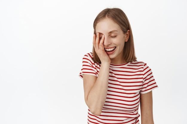 化粧をせずに清潔で自然な肌を持つ美しい若い女性は、彼女の顔に触れ、目を閉じて笑って幸せに笑い、白い壁にリラックスしたポーズで立っています。
