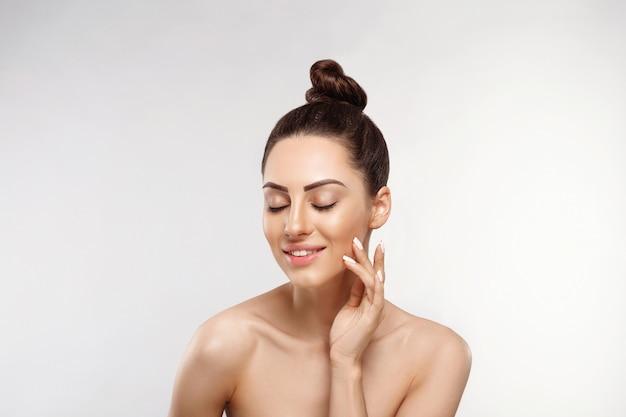 깨끗하고 완벽 한 피부를 가진 아름 다운 젊은 여자. 자연 누드 메이크업과 그녀의 얼굴을 만지고 뷰티 모델의 초상화. 스파, 피부 관리 및 웰빙.