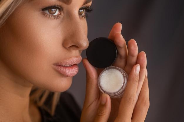 깨끗하고 완벽한 피부를 가진 아름다운 젊은 여성이 입술 설탕 스크럽을 사용합니다.