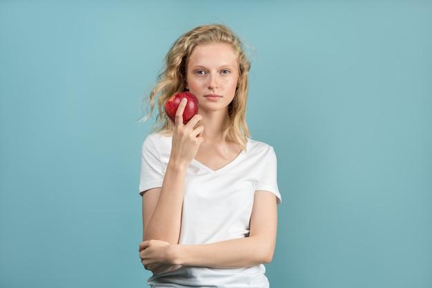 Красивая молодая женщина с чистой молодой свежей кожей без макияжа с длинными вьющимися волосами держит яблоко