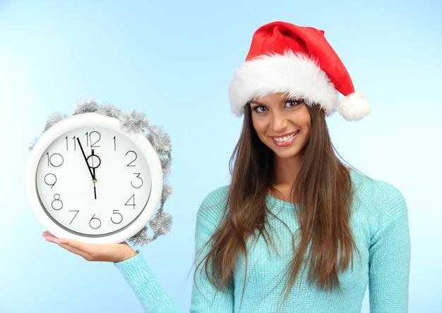 파란색 표면에 시계와 함께 아름 다운 젊은 여자