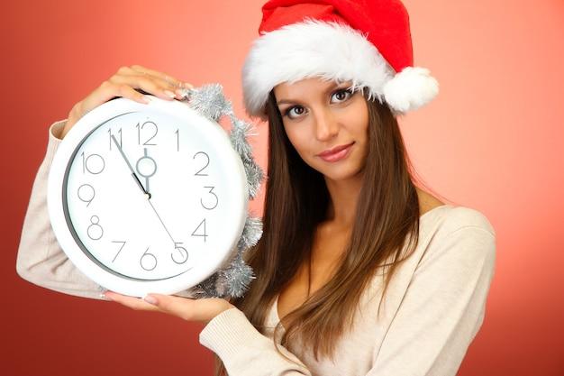 빨간색 배경에 시계와 함께 아름 다운 젊은 여자