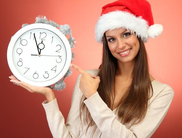 Красивая молодая женщина с часами, на красном фоне