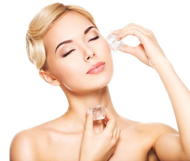 目を閉じた美しい若い女性は、顔に氷を適用します-白で隔離。