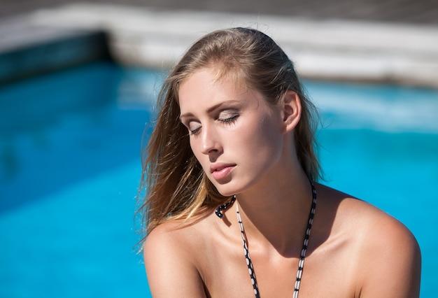 눈을 감은 아름다운 젊은 여성이 수영장에서 휴식을 취하고 일광욕을 즐깁니다