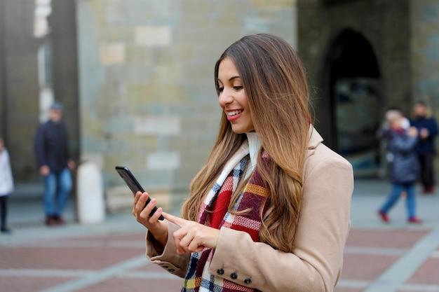 Красивая молодая женщина с пальто и шарфом печатает на своем телефоне на городской улице