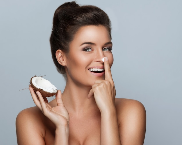 Beautiful young woman with a coconut and moisturizing cream