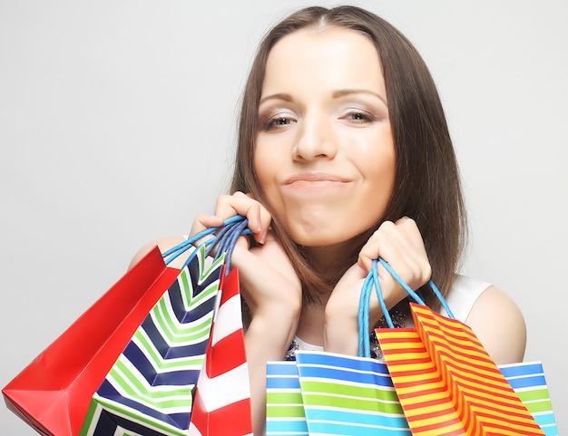 Красивая молодая женщина с цветными сумками на сером фоне Premium Фотографии
