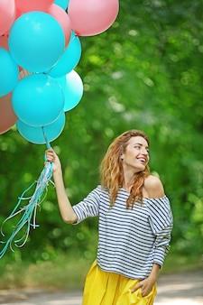 Красивая молодая женщина с красочными воздушными шарами в парке