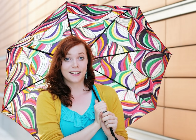 Beautiful young woman with colorful umbrella