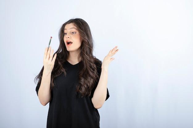Bella giovane donna con pennello cosmetico in piedi sul muro bianco.