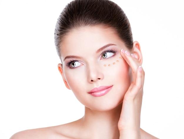 Bella giovane donna con fondotinta cosmetico su una pelle. concetto di trattamento di bellezza.