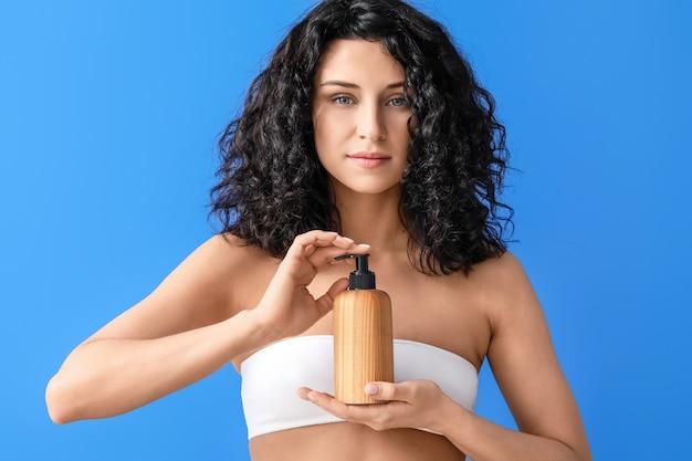 色の表面に化粧品を持つ美しい若い女性