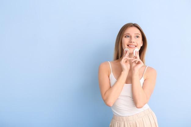 青にコットンパッドを持つ美しい若い女性