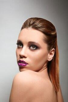 色の背景に創造的なメイクと美しい若い女性