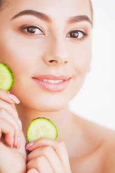 Beautiful young woman with cucumbers on eyes.