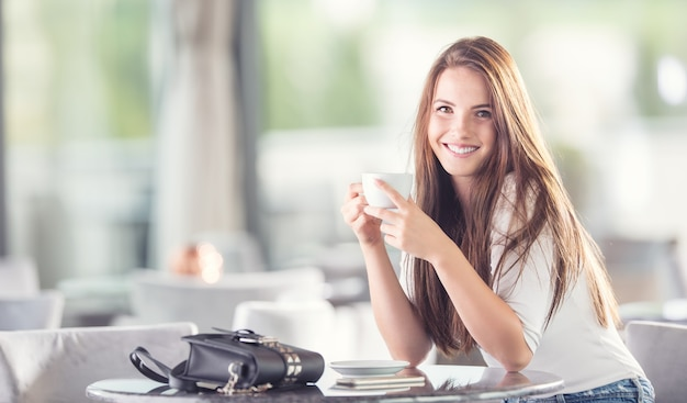 Beautiful young woman with a cup of coffee or tea in the cafe.