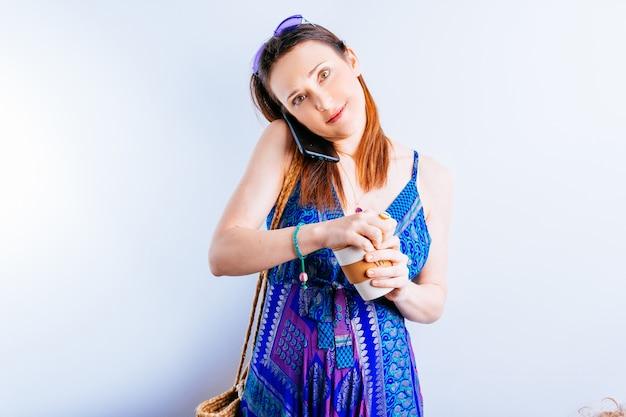 흰색 바탕에 전화 통화를 하는 커피 여름 드레스와 보라색 안경을 쓴 아름다운 젊은 여성