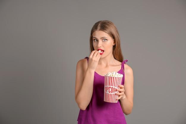 Красивая молодая женщина с чашкой попкорна на серой поверхности