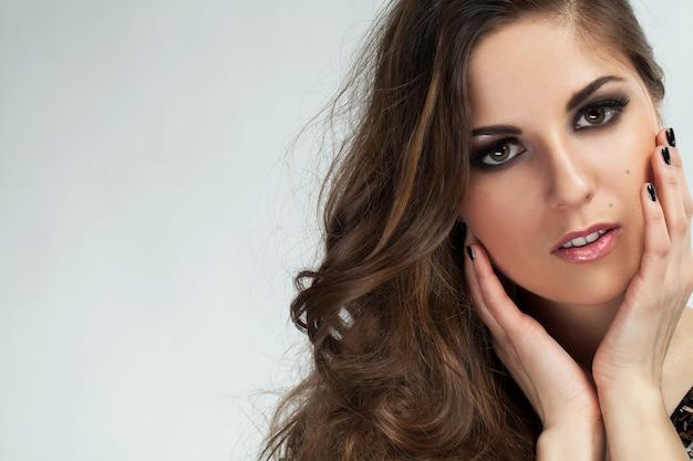 Красивая молодая женщина с кудрями и макияж