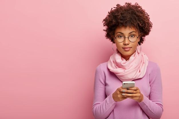 Bella giovane donna con i capelli scuri ricci, rimane in contatto, usa gadget moderni, crea il suo blog