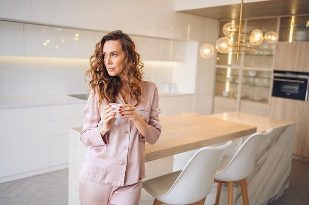 居心地の良いピンクのパジャマで週末の朝にコーヒーを飲む巻き毛の美しい若い女性。北欧スタイルの白いキッチンモダンなインテリアの女性。