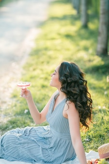 곱슬 머리를 가진 아름 다운 젊은 여자는 피 사쿠라 정원에서 핑크 샴페인을 마신다. 자연 속에서 피크닉. 봄.