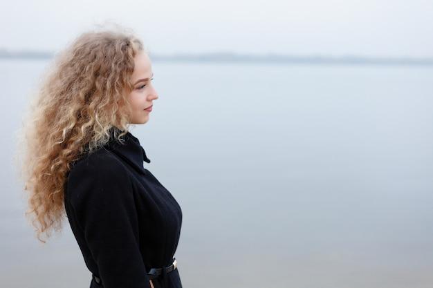 巻き毛、緑色の目を持つ美しい若い女性。落ち葉で覆われた、天気の良い秋の公園でリラックスしたカジュアルな服を着た女の子。