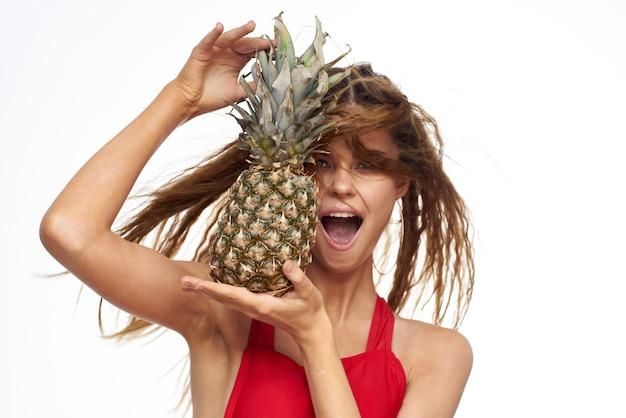 パイナップルと赤い水着トロピカルイメージで巻き毛の美しい若い女性