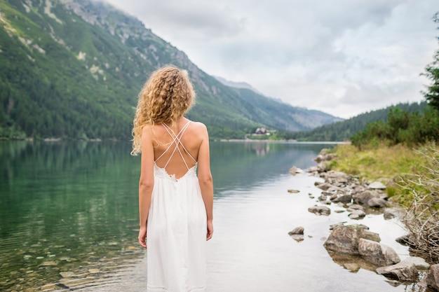 白いドレスを着た巻き毛の美しい若い女性が近くに立っています