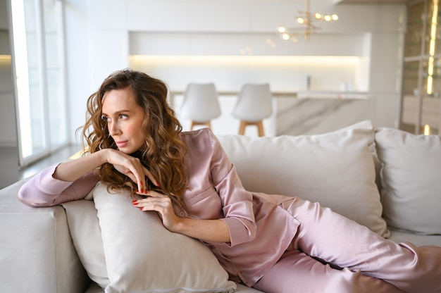 Beautiful young woman with curly hair in  pink pajamas lying at white couch sofa in the morning. scandinavian style living room & kitchen interior.
