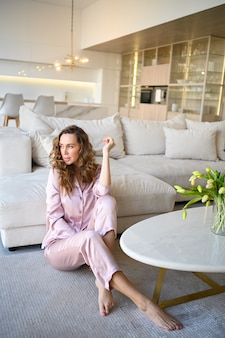 Beautiful young woman with curly hair in  pink pajamas sitting near white couch sofa in the morning. scandinavian style living room & kitchen interior.