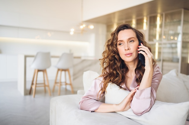Beautiful young woman with curly hair in  pink pajamas at white couch in the morning. lady speaking phone in scandinavian style living room interior.