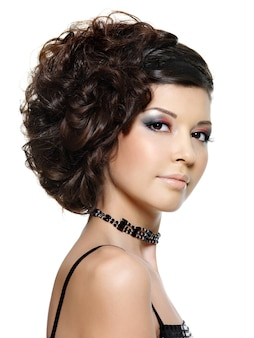 Beautiful young woman with curly hairstyle and bright makeup - on white wall