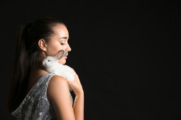 Красивая молодая женщина с милым кроликом на темной поверхности