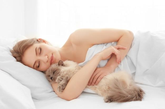 自宅のベッドに横たわっているかわいい猫と美しい若い女性