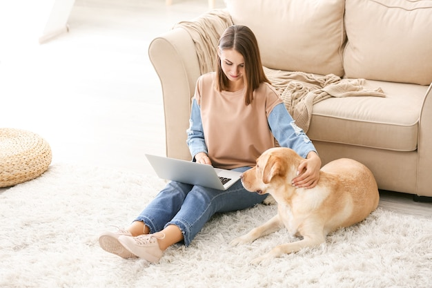 Красивая молодая женщина с милой собакой, используя ноутбук дома