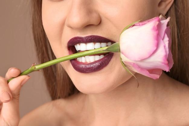 暗い口紅と口の中の花、クローズ アップを持つ美しい若い女性