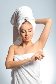 Beautiful young woman with deodorant on light