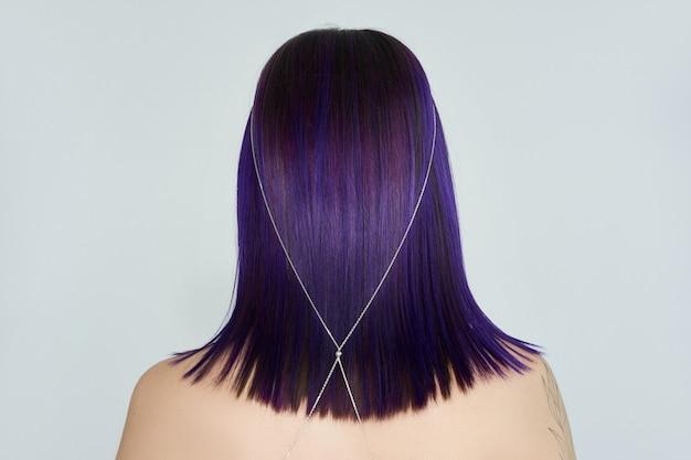 染めた髪の紫がかった赤い色、明るい美容メイクのクローズアップを持つ美しい若い女性。強い色の髪