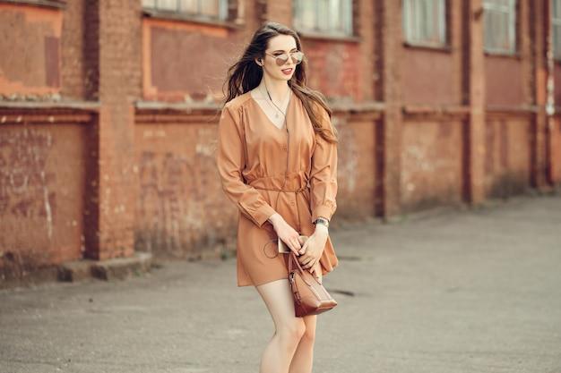 歩道の上を歩くイヤホンと美しい若い女性