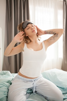 Beautiful young woman with eye cover mask waking up with positive attitude.