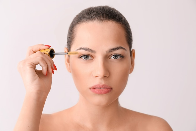 Beautiful young woman with eyelash extensions and special brush