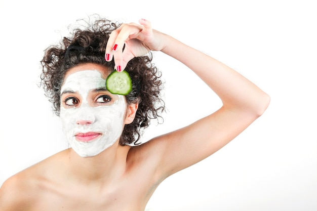Beautiful young woman with face mask holding cucumber slice against white background