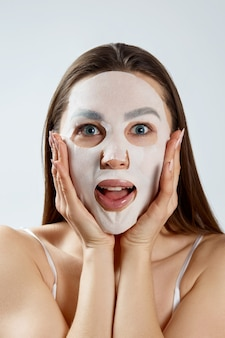 Beautiful young woman with facial mask. cosmetic procedure. girl beauty spa and cosmetology.