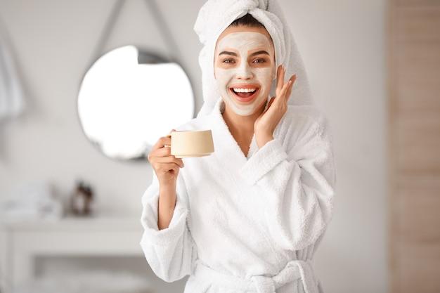 バスルームでコーヒーを飲みながら顔のマスクを持つ美しい若い女性