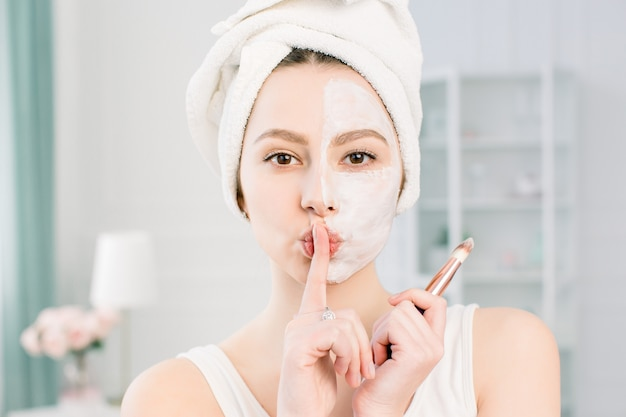 Beautiful young woman with facial mask on light studio showing silence sign