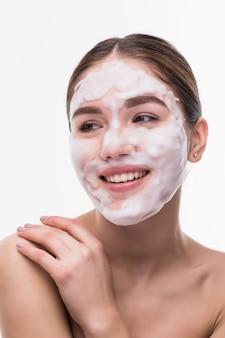 Bella giovane donna con la maschera facciale sulla parete bianca