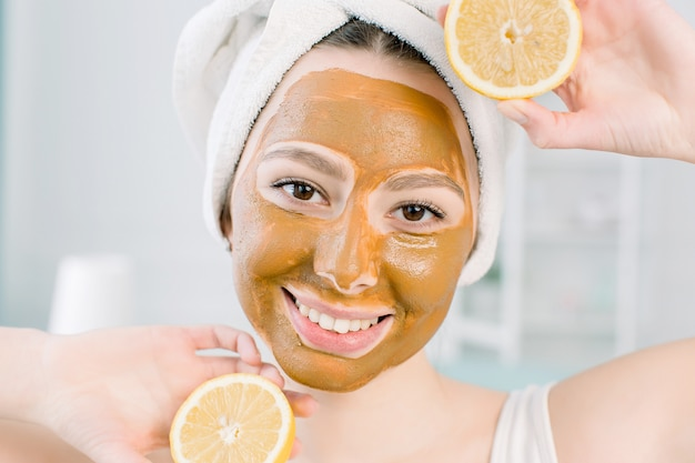 Beautiful young woman with facial mud mask and halfs of lemon on light space in spa center
