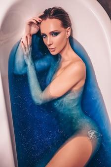 아름 다운 젊은 여자 패션 메이크업, 컬러 블루 우주 목욕 폭탄 물이 가득한 복고풍 욕조에서 목욕 포즈. 스파 및 뷰티 살롱 개념, 바디 및 스킨 케어.